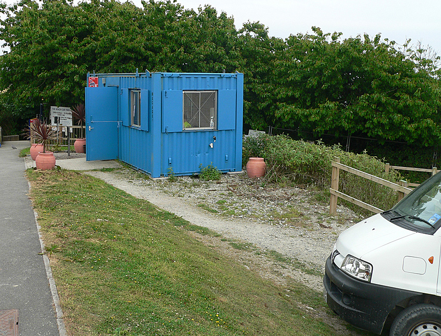The South West Coast Path partially blocked by a portacabin, fencing and parked vehicles